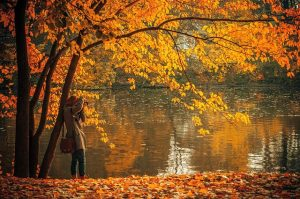 A woman by a lake in the fall