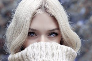 The eyes of a woman in a white sweater